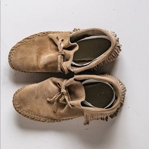 Mink color moccasin booties with fringes.